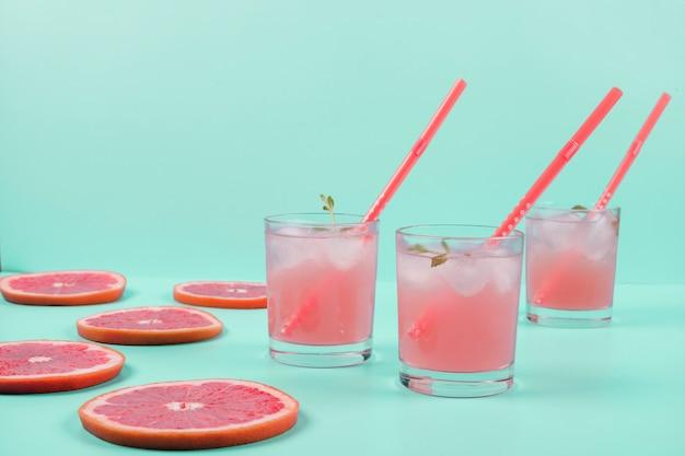 Três copos de suco de grapefruit e fatias sobre o pano de fundo de hortelã