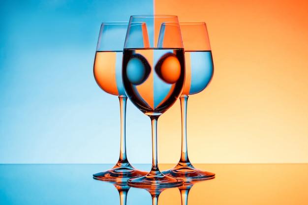 Três copos de vinho com água sobre o fundo azul e laranja.