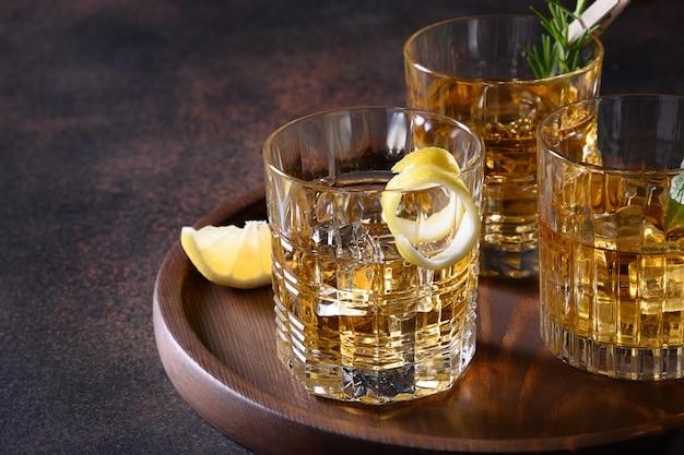Três copos de whisky frio servido com gelo com alecrim, cascas de limão no marrom. copie o espaço.