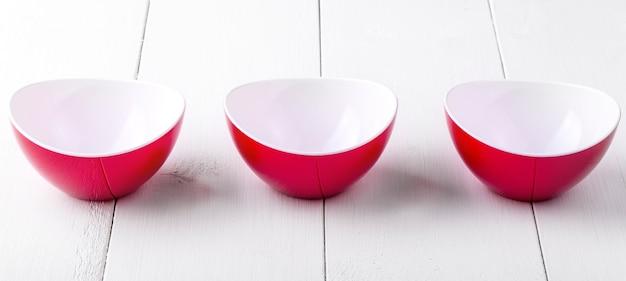 Três copos vermelhos em uma mesa de madeira branca