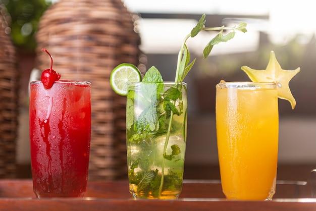 Três coquetéis de frutas coloridas gin tônica em copos no balcão de bar em cachorro ou restaurante
