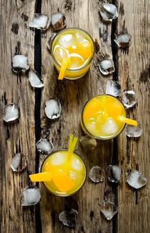 Três coquetéis de laranjas frescas com gelo e palha no fundo de madeira