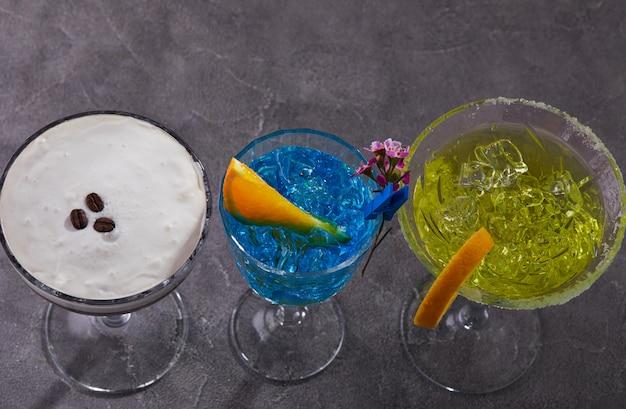 Três coquetéis espresso martini, curaçao azul e thea em pé em uma linha em uma mesa cinza