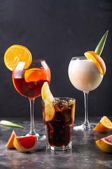 Três coquetéis refrescantes em copo colocado na mesa. os copos são decorados com uma fatia de laranja