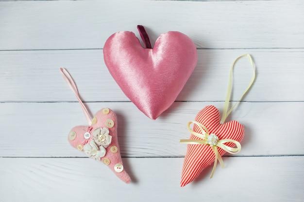 Três corações cor-de-rosa de matéria têxtil no fundo de madeira. decoração de dia dos namorados de estilo vintage