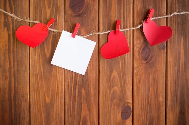 Três corações de amor pendurado no fundo de textura de madeira, conceito de cartão de dia dos namorados