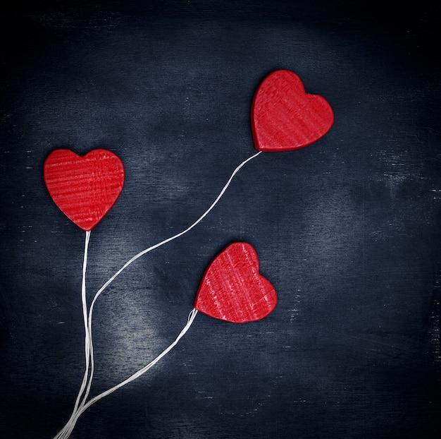 Três corações de madeira vermelhas em uma corda branca