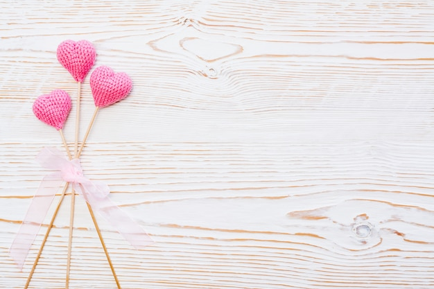 Três corações de malha rosa em varas amarradas com fita rosa em um branco de madeira