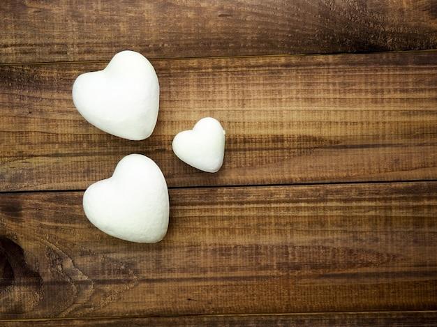 Três corações em um fundo escuro de madeira, conceito de dia dos namorados