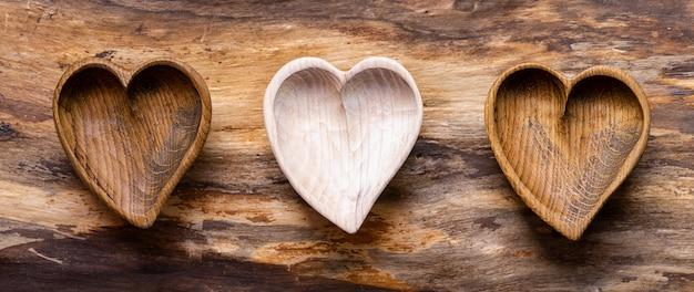 Três corações feitos de madeira clara e escura sobre um fundo de madeira natural
