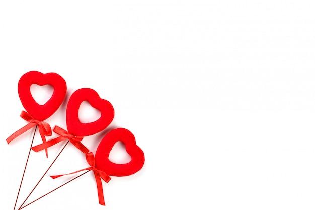 Três corações vermelhos com arcos em uma superfície branca