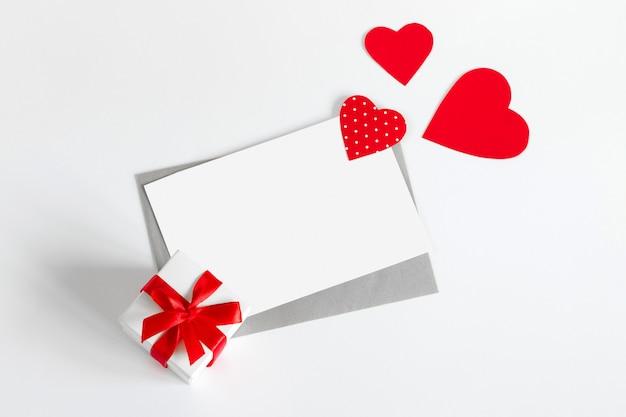 Três corações vermelhos e uma caixa de presente, uma folha de papel branca e uma carta