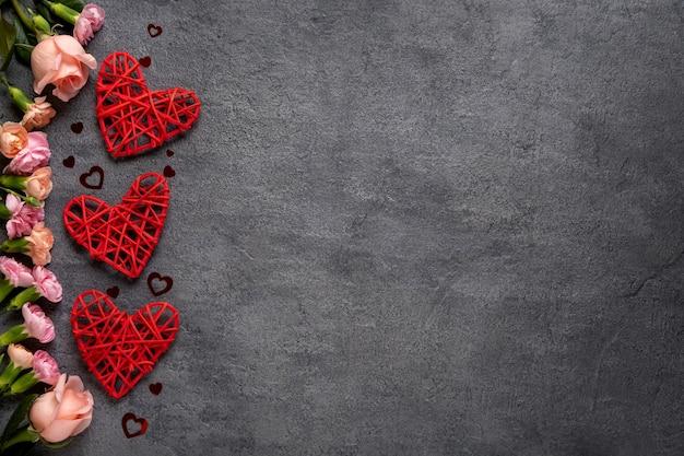 Três corações vermelhos em um fundo cinza de concreto. conceito de dia dos namorados. copie o espaço. vista de cima.