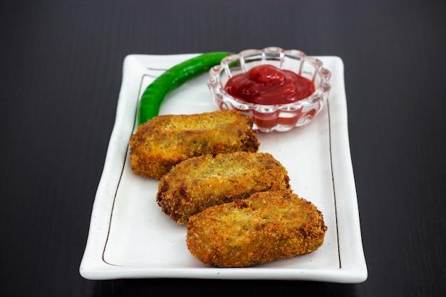 Três costeletas torradas fritadas douradas servidas com molho ou ketchup de tomate na placa branca, preparam-se para a ramadã iftar. fundo de madeira foco seletivo. espaço da cópia