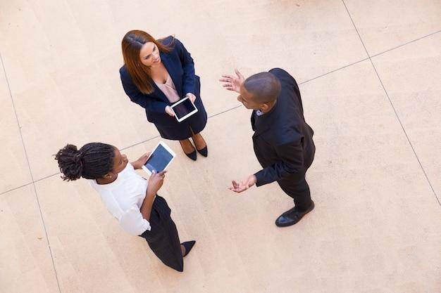 Três, coworkers, discutir, projeto, em, escritório, lobby