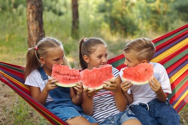 Três crianças alegres comem melancia e brincam, ao ar livre, sentadas em uma rede colorida. diversão e lazer de verão