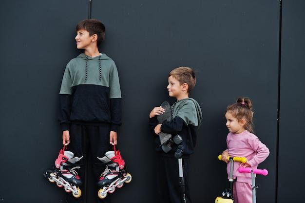 Três crianças ao ar livre contra uma parede preta moderna. a família de esportes passa o tempo livre ao ar livre com patinetes e patins.