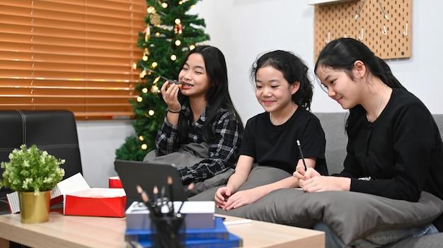 Três crianças asiáticas aprendendo aula online juntos em casa.