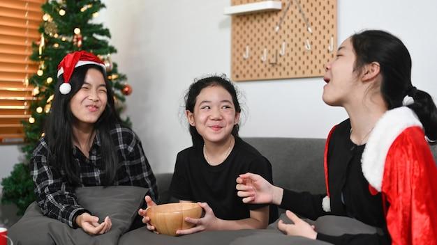 Três crianças asiáticas sentadas perto da árvore de natal em casa.
