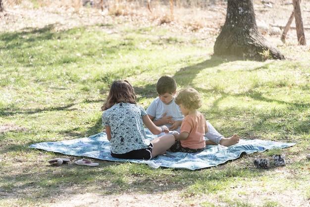 Três crianças brancas brincam e passam férias alternativas em uma caravana