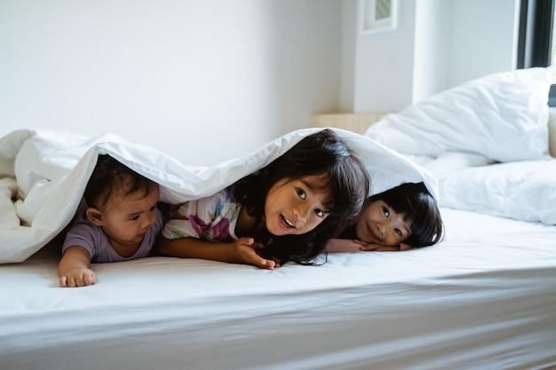 Três crianças brincam e se escondem debaixo das cobertas
