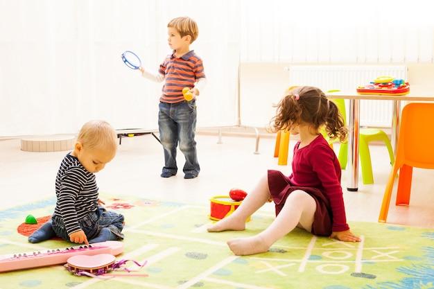 Três crianças brincando na sala de jogos. as crianças fantasiam que são músicos. a menina toca bateria, o primeiro menino toca xilofone, o segundo menino toca piano.