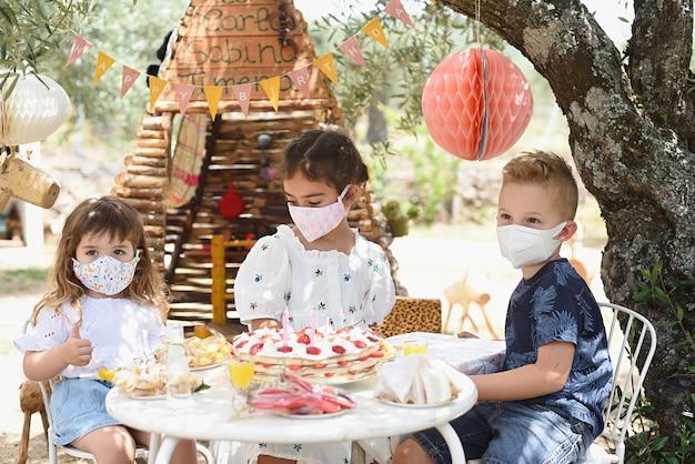 Três crianças comemorando aniversários com máscaras ao ar livre