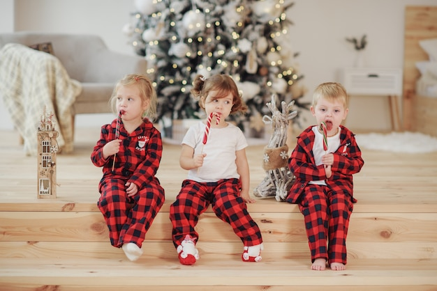Três crianças de pijama vermelho deitam-se em uma cama em uma sala de estar aconchegante e comem balas doces em um palito. conceito de natal. feriado em casa