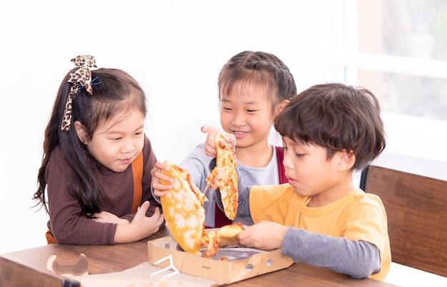 Três crianças, é, comer, entrega pizza, em, sala aula