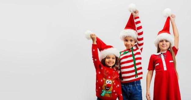 Três crianças em fantasias de natal segurando chapéus vermelhos de papai noel em saudação