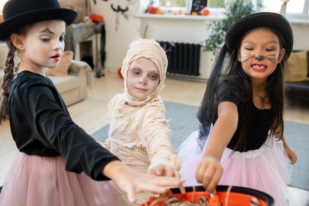 Três crianças em fantasias inteligentes de halloween levando guloseimas