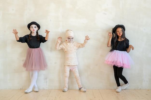 Três crianças em trajes de halloween em pé ao longo de uma parede branca