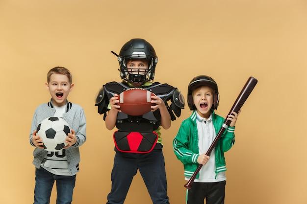 Três crianças felizes mostram trajes diferentes do esporte
