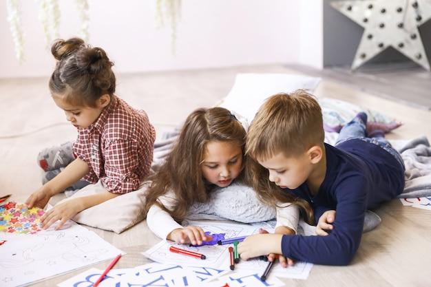 Três crianças focadas estão brincando no chão e desenhando livros para colorir