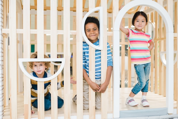 Três crianças fofas e alegres de etnias asiáticas, brancas e africanas brincando juntas em um centro de lazer para crianças