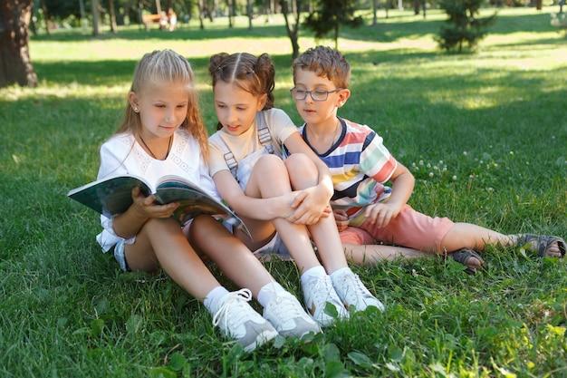 Três crianças lendo um livro juntas na grama do parque