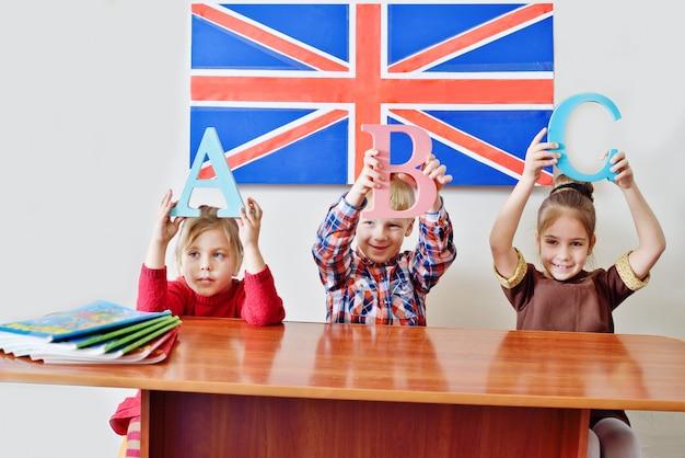Três crianças na aula de inglês
