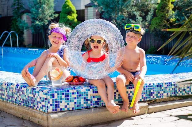 Três crianças no verão sentam-se à beira da piscina de óculos escuros e bebem limonada