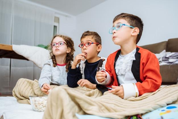 Três crianças pequenas brincando alegremente juntas no apartamento