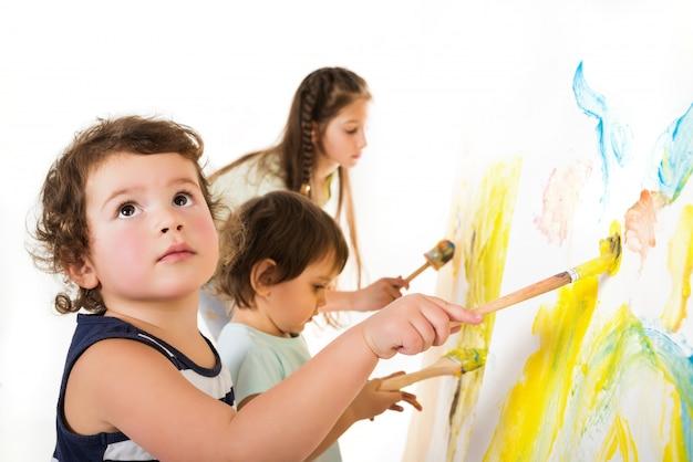 Três crianças pintam com pincéis e tintas