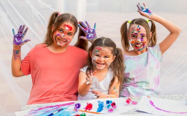 Três crianças pintam com tintas. meninas sorriem alegremente e se divertem.