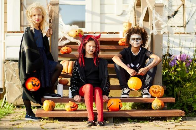 Três crianças posando pela casa decorada no halloween
