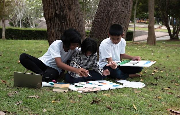 Três crianças sentadas no chão de grama verde, pintando uma tela colorida e conversando, fazendo atividades juntas com sentimento de felicidade, em um parque