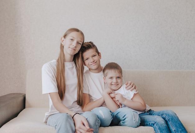 Três crianças, uma menina e dois meninos em camisetas brancas e jeans azuis, sentam-se abraçados no sofá de casa e sorriem.