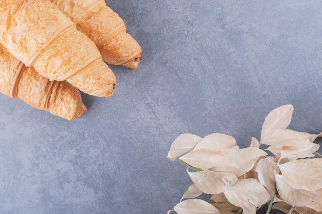 Três croissant francês fresco em fundo cinza.