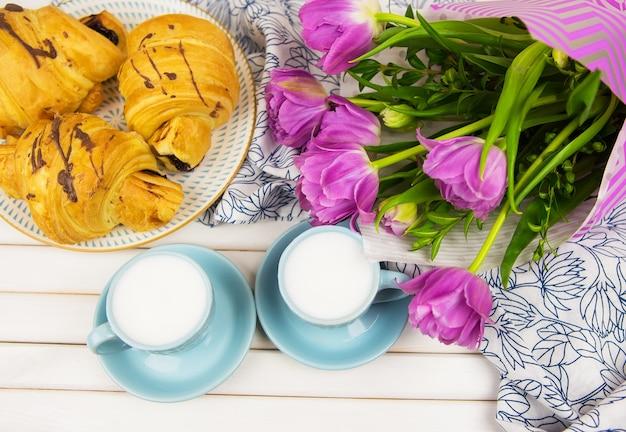 Três croissants, duas xícaras de café na mesa e um buquê de lindas tulipas em close-up