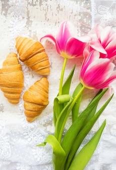 Três croissants e tulipas rosa brilhantes na toalha de mesa de renda.
