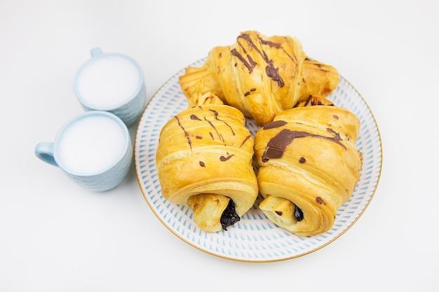 Três croissants recém-assados em um prato de cerâmica branca, duas xícaras de café