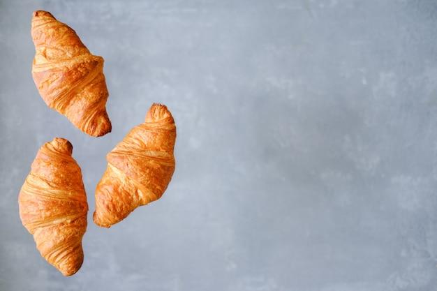 Três croissants recentemente cozidos que voam no fundo cinzento. lugar para texto. conceito de padaria criativa.