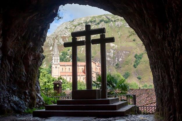 Três cruzes dentro de uma caverna em frente à catedral de covadonga. astúrias, espanha